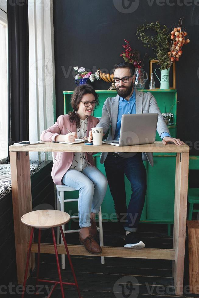 equipe moderna trabalhando no café com laptop, smartphone com café foto
