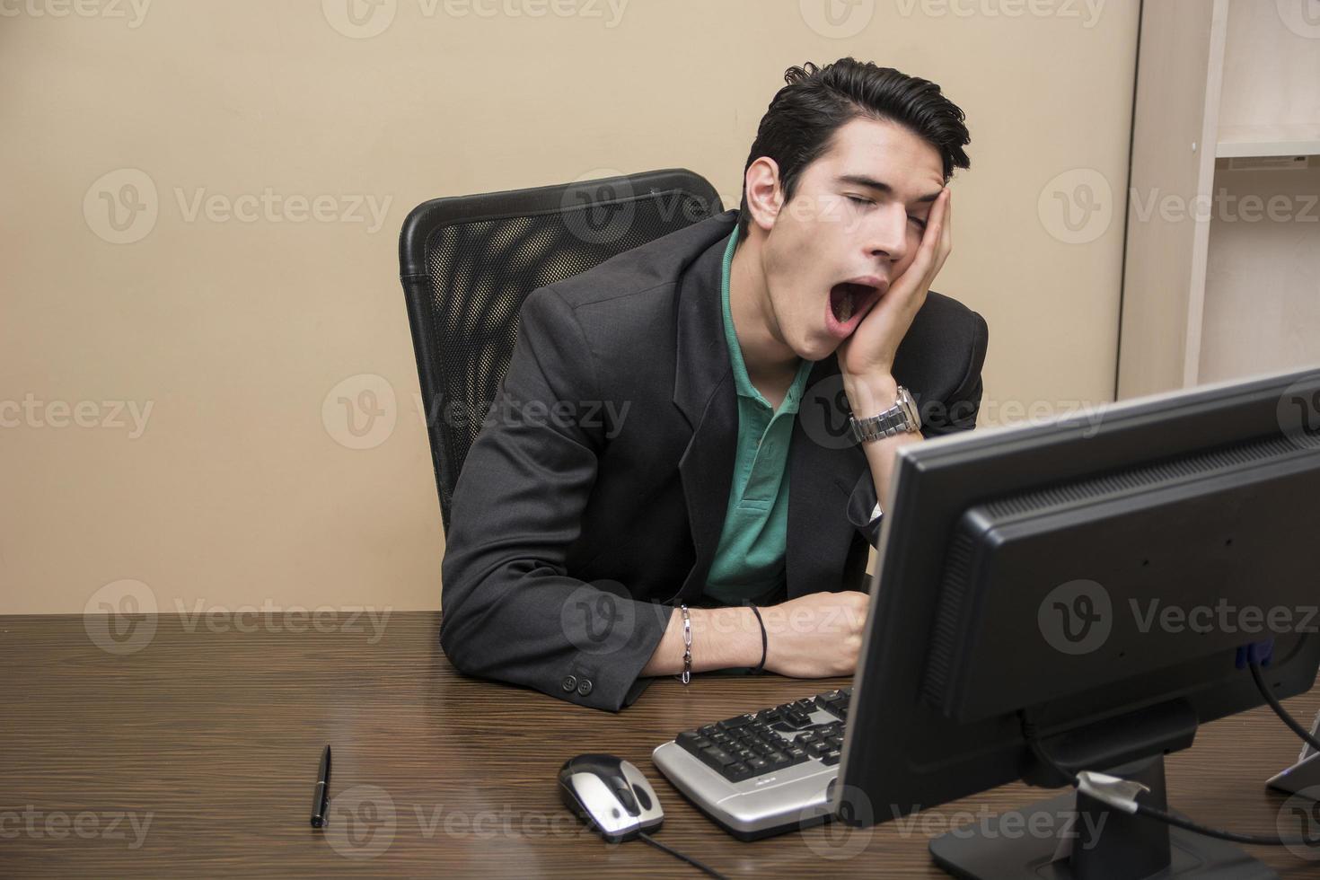 cansado jovem empresário entediado sentado no escritório bocejando foto