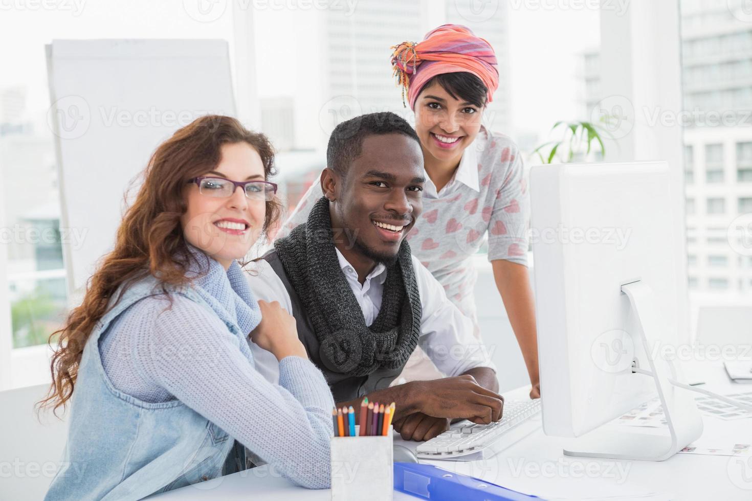 colegas de trabalho posando e olhando para a câmera a sorrir foto