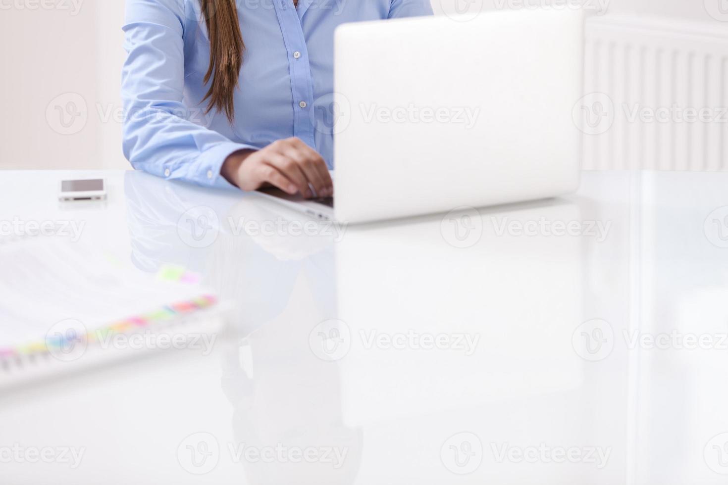 close-up vista de mulher bonita usando o laptop na mesa foto