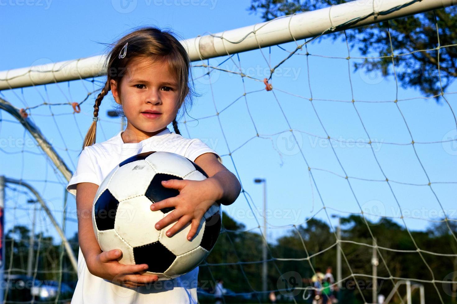 menina, segurando uma bola de futebol foto