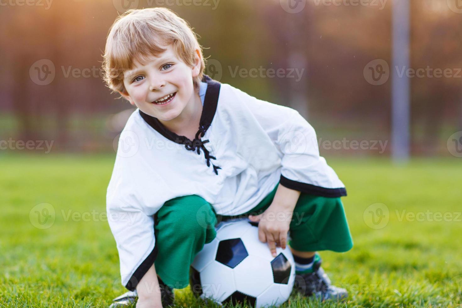 menino loiro de 4 jogando futebol com campo de futebol onl foto