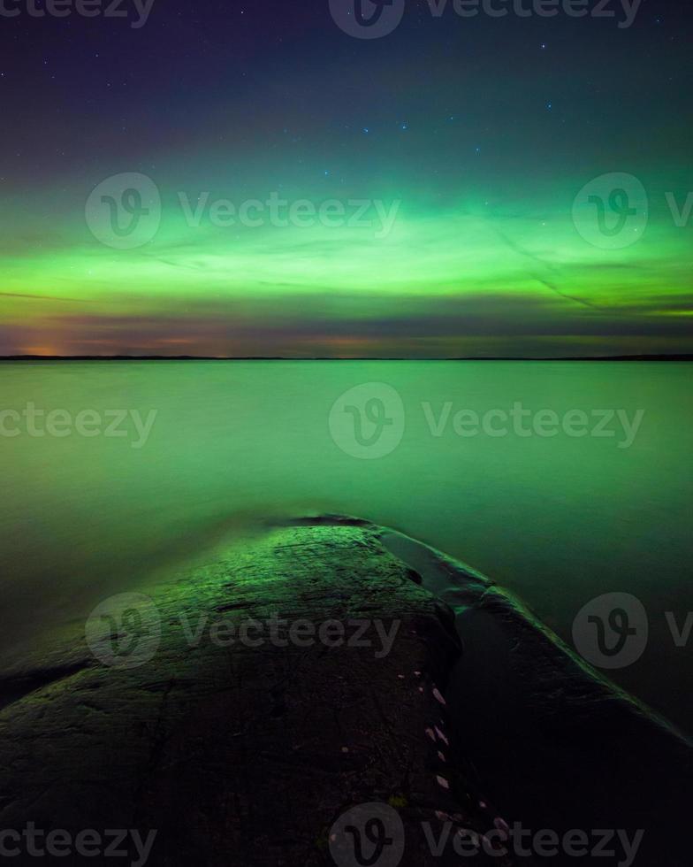 luzes do norte sobre o lago na Finlândia foto