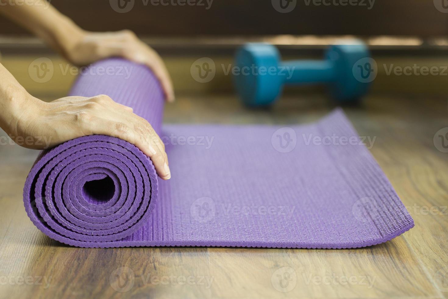 mãos rolando tapete de ioga roxo com haltere azul atrás foto
