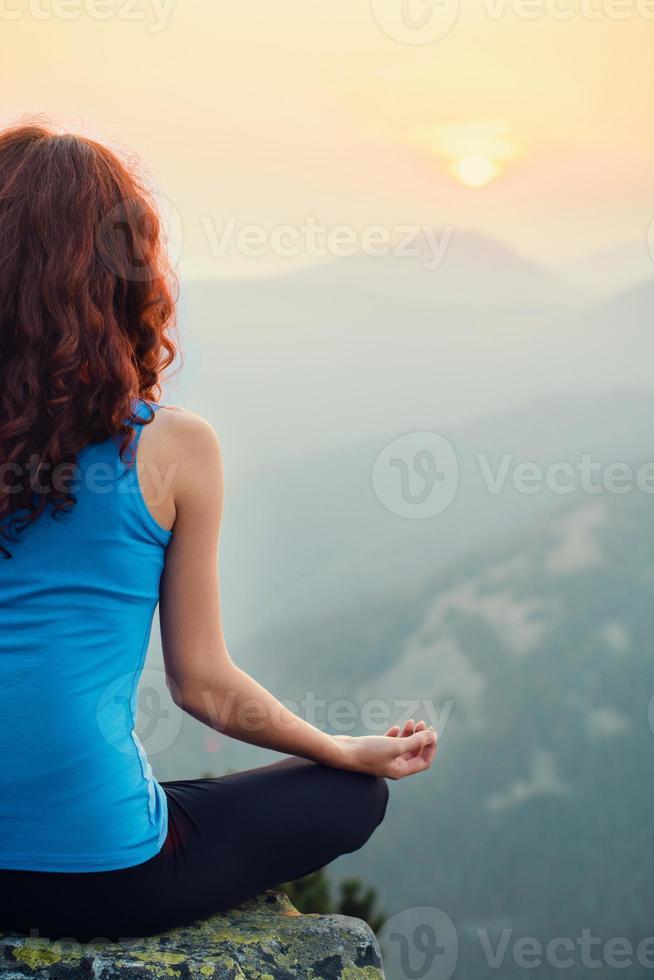 mulher meditando na natureza no pôr do sol foto