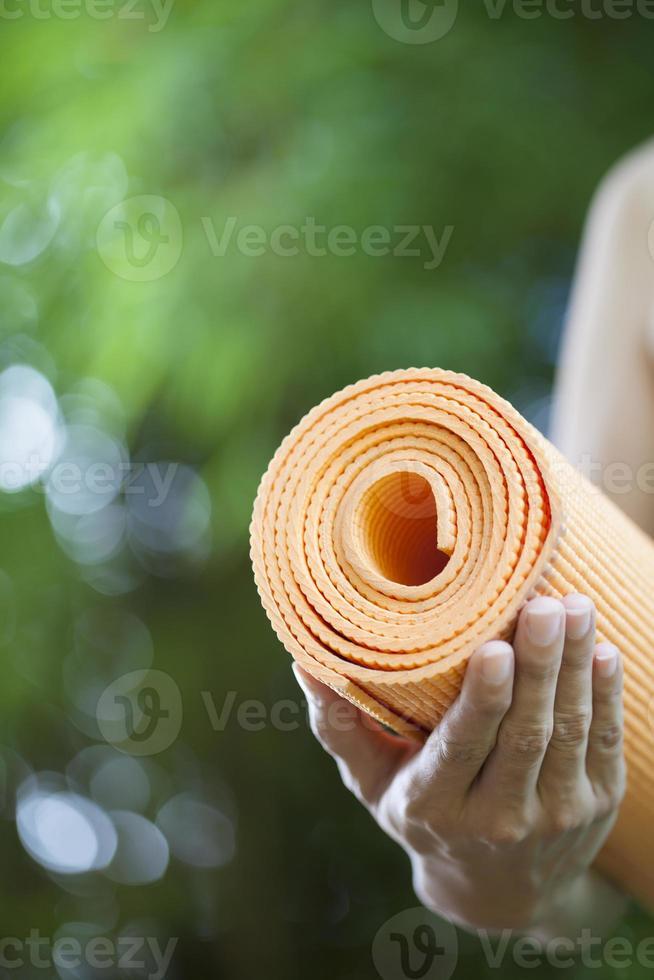 jovem mulher segurando um tapete de ioga foto