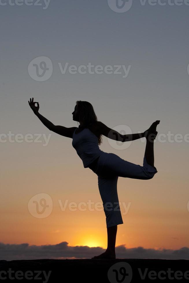 meditação de ioga na praia ao nascer do sol foto