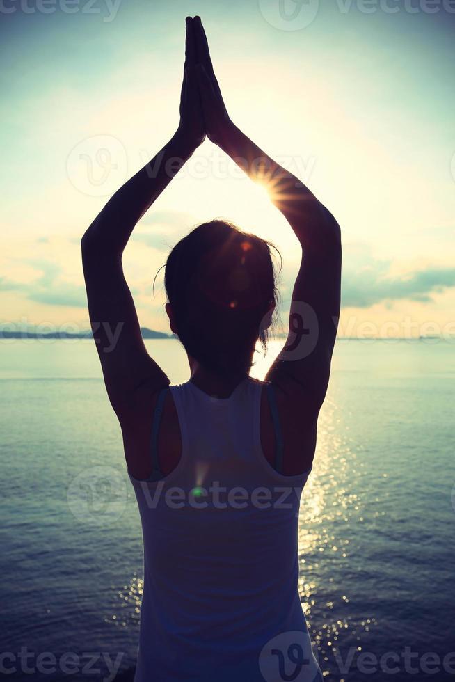 meditação de mulher ioga saudável à beira-mar do nascer do sol foto