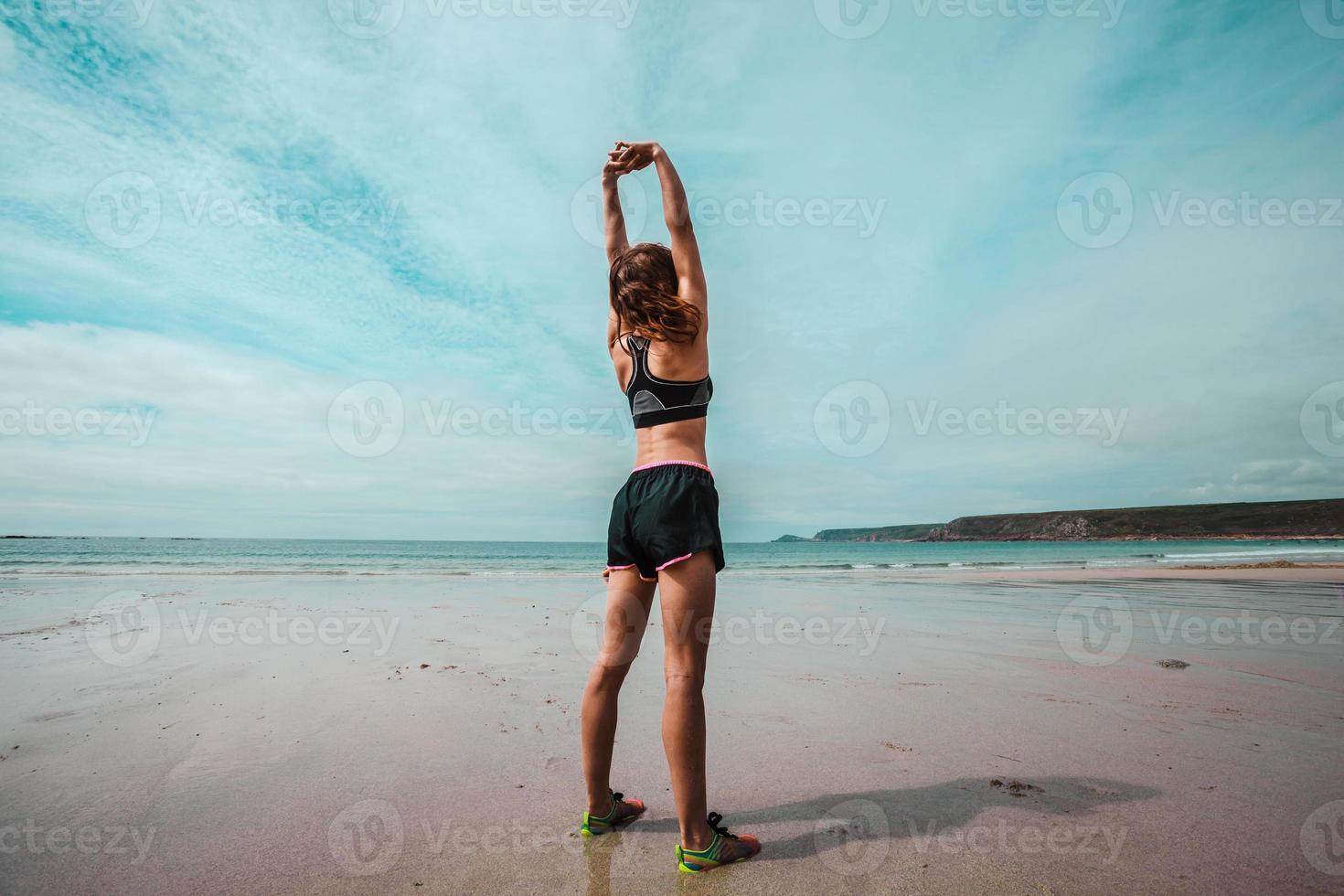 jovem mulher atlética, estendendo-se na praia foto