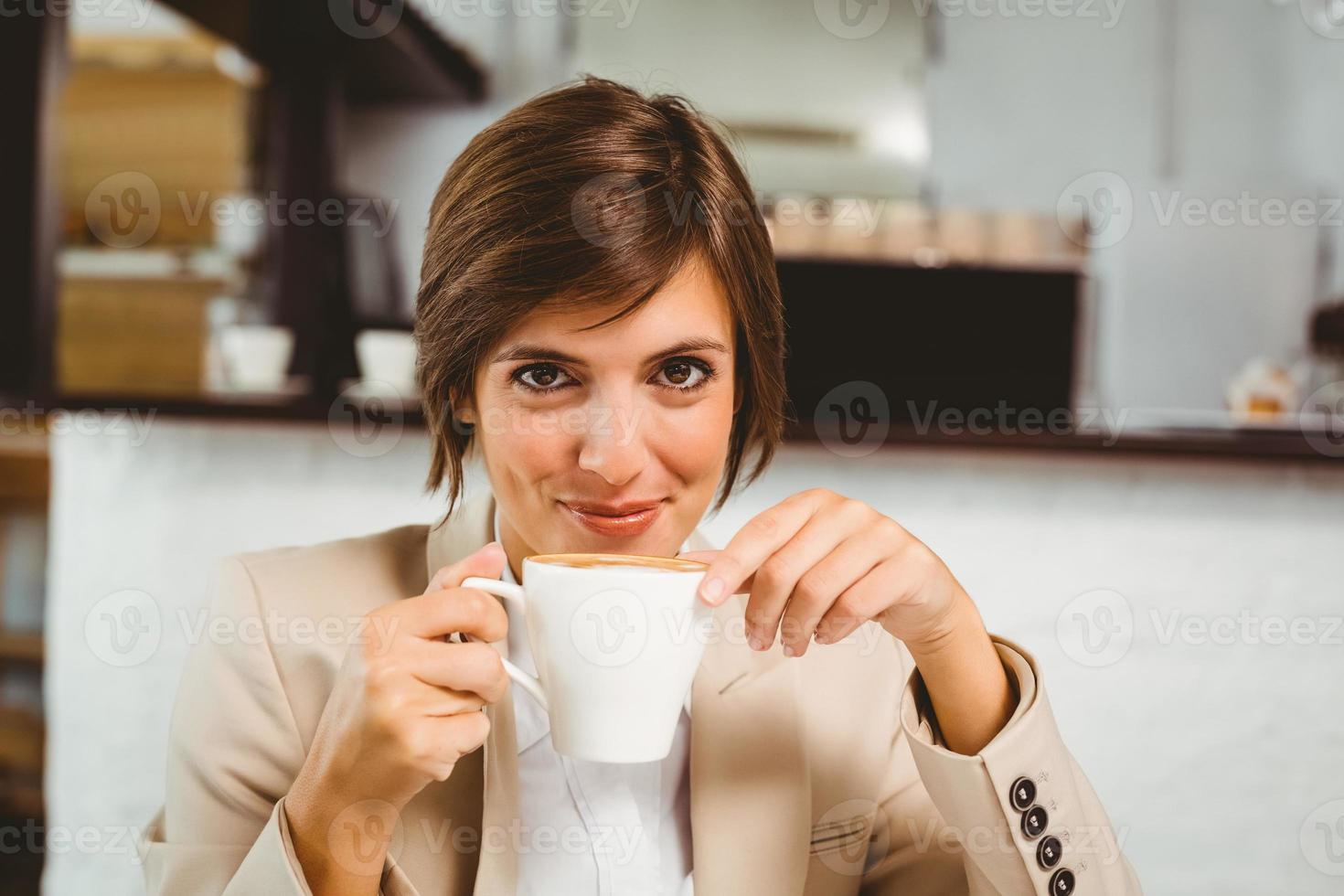 bonita empresária desfrutando de seu café foto