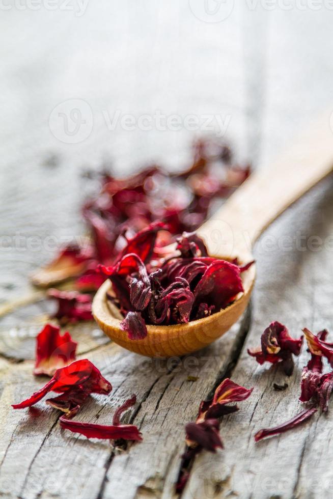 chá de hibisco seco em colher de madeira foto