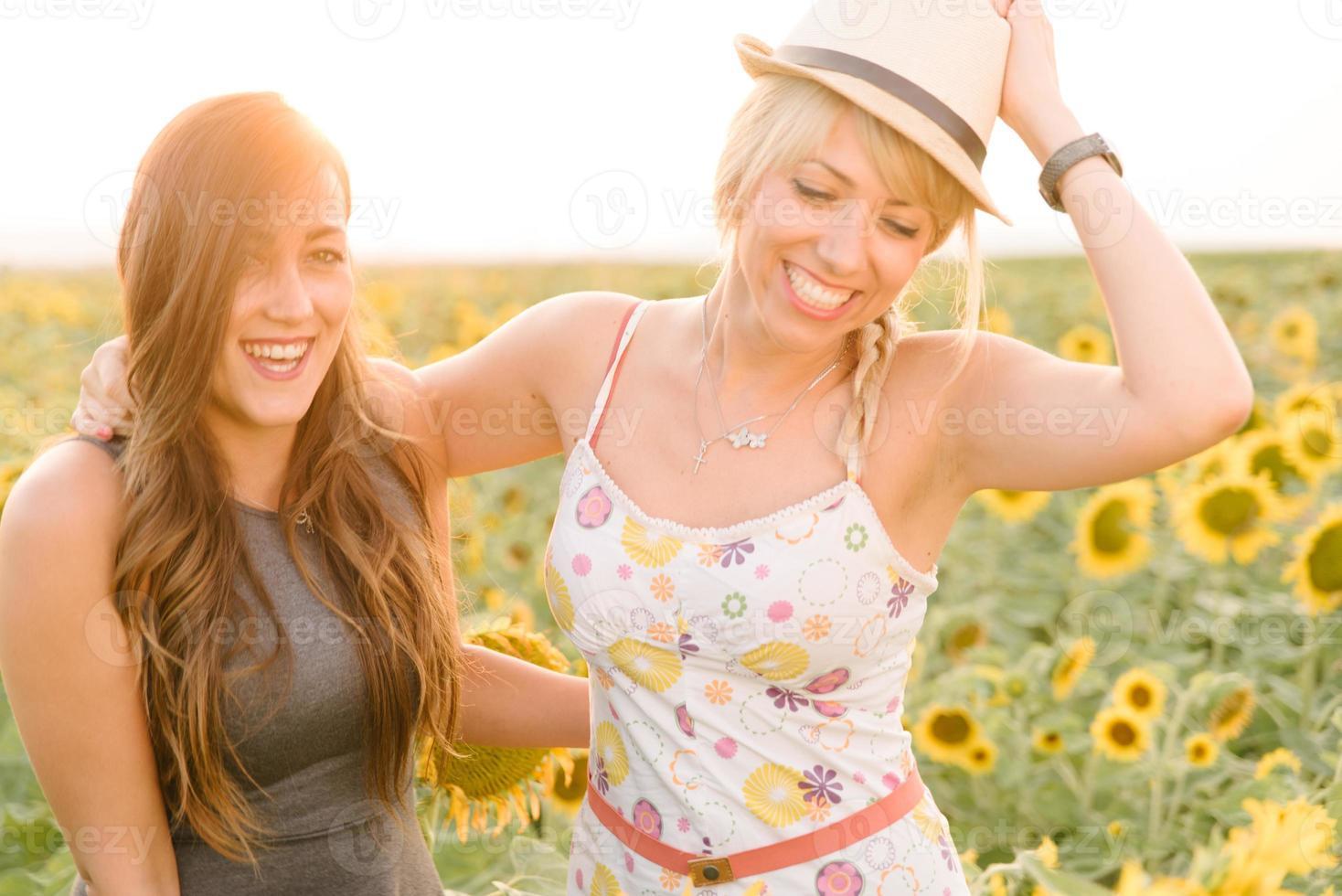 garotas desfrutando de um passeio no campo de girassol. foto