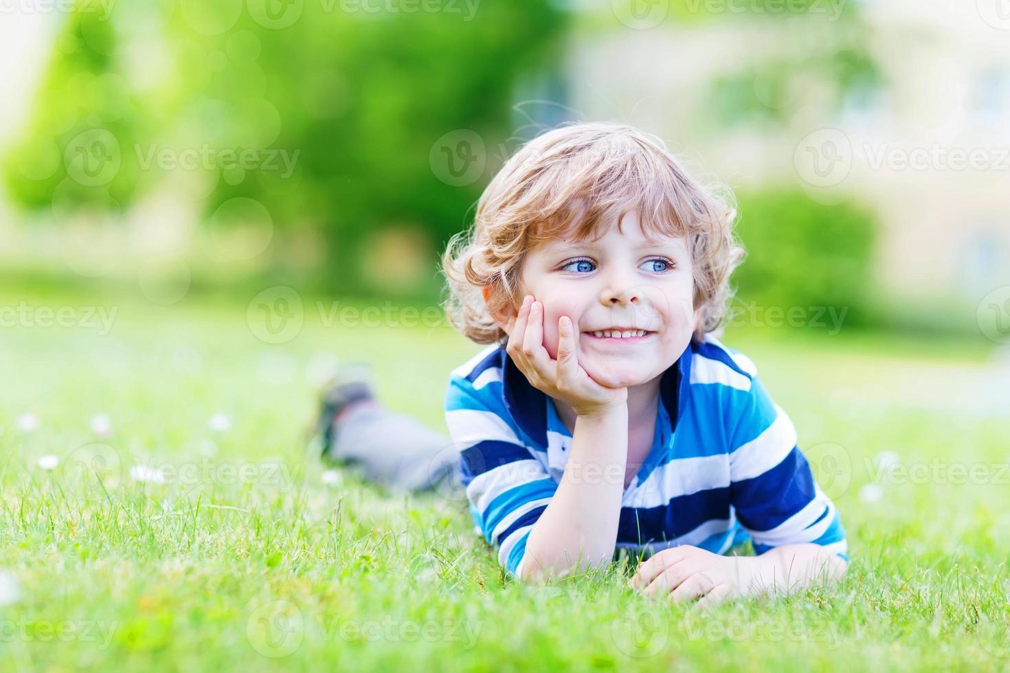 criança feliz desfrutando no campo de grama e sonhando foto