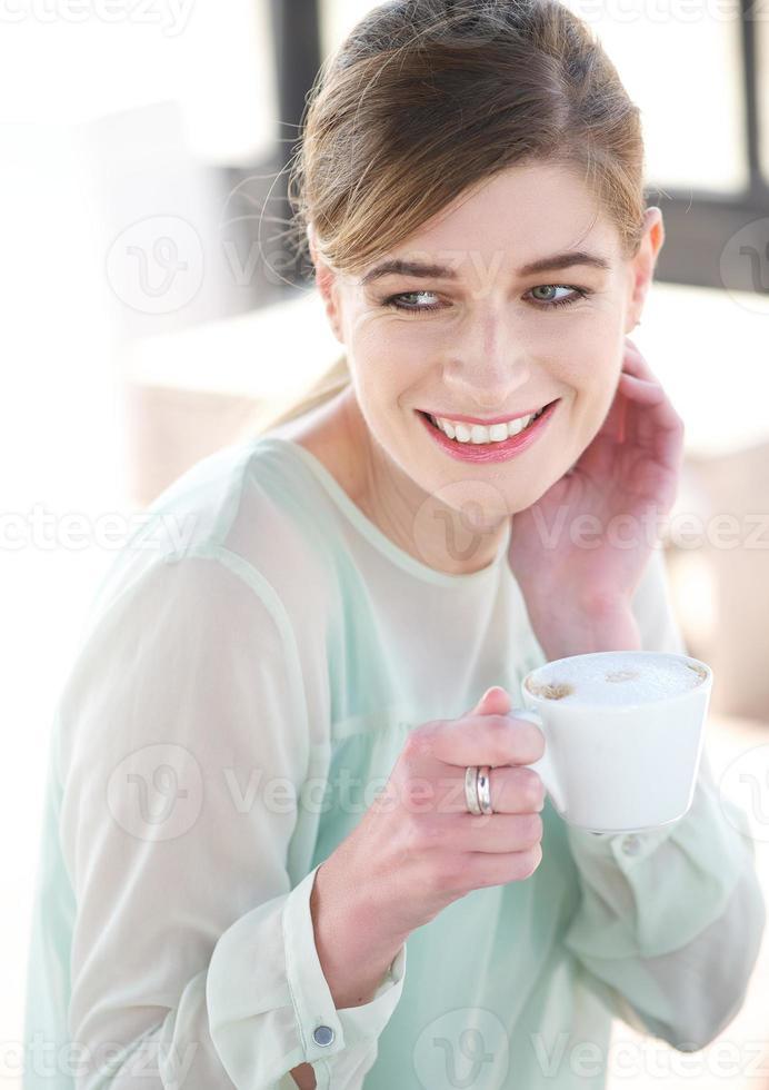 jovem sorrindo e desfrutando de uma xícara de café foto
