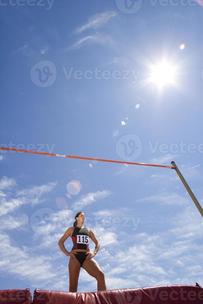 jovem atleta feminina por bar, vista de ângulo baixo (reflexo de lente) foto