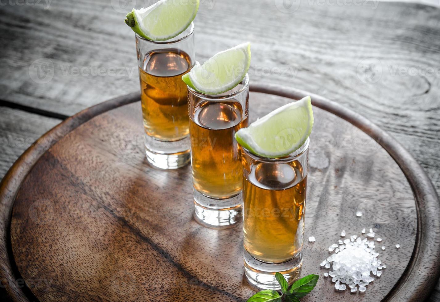 copos de tequila na placa de madeira foto