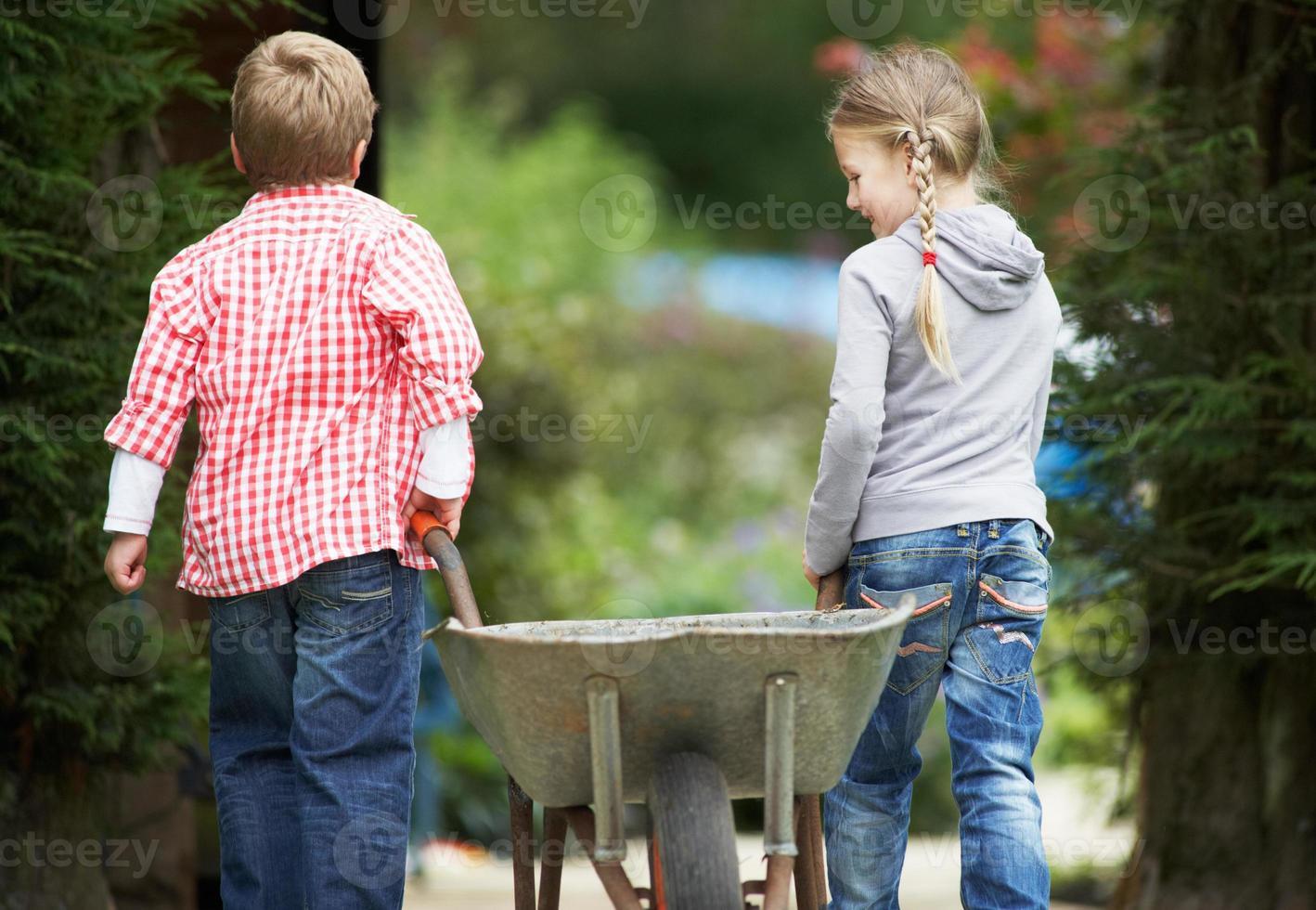 duas crianças brincando com carrinho de mão no jardim foto