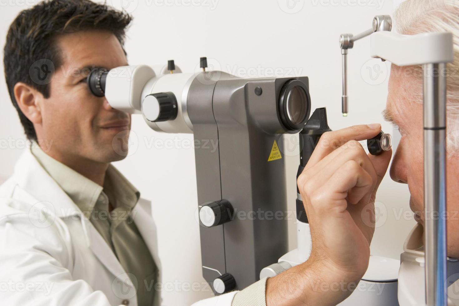 médico verificando os olhos do paciente foto