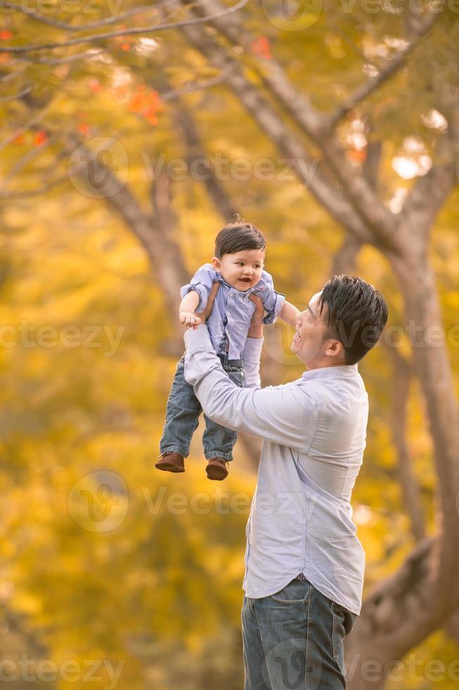 asiático pai e filho se divertindo ao ar livre foto
