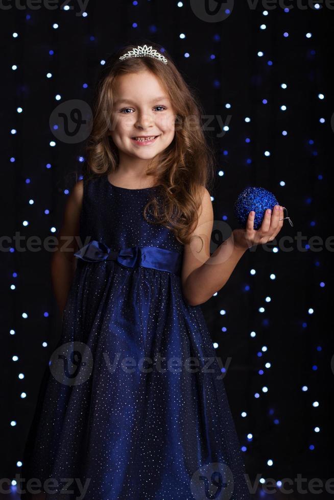 menina criança bonita está segurando uma bola de natal azul foto