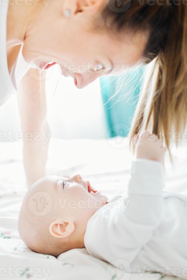 bebê brincando com o cabelo da mãe foto