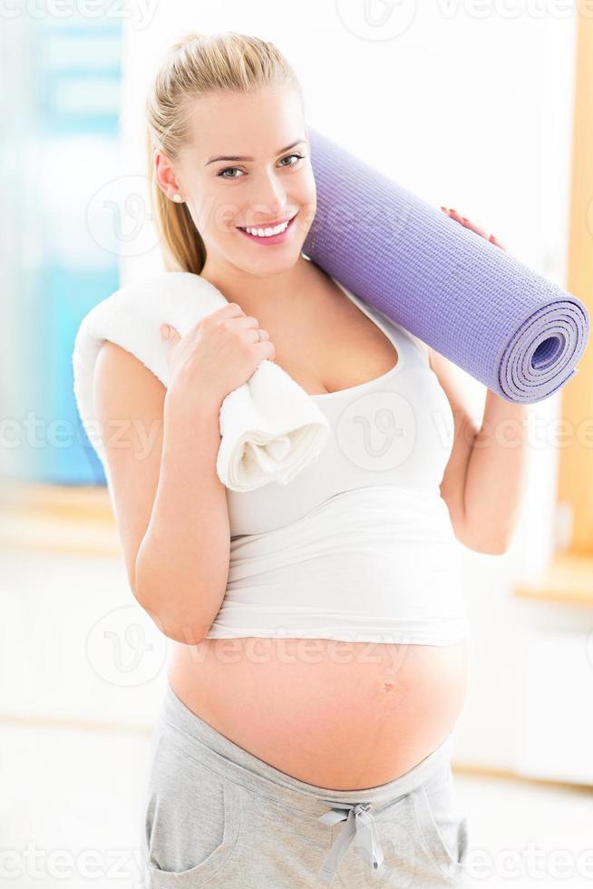 mulher grávida segurando o tapete de ioga foto