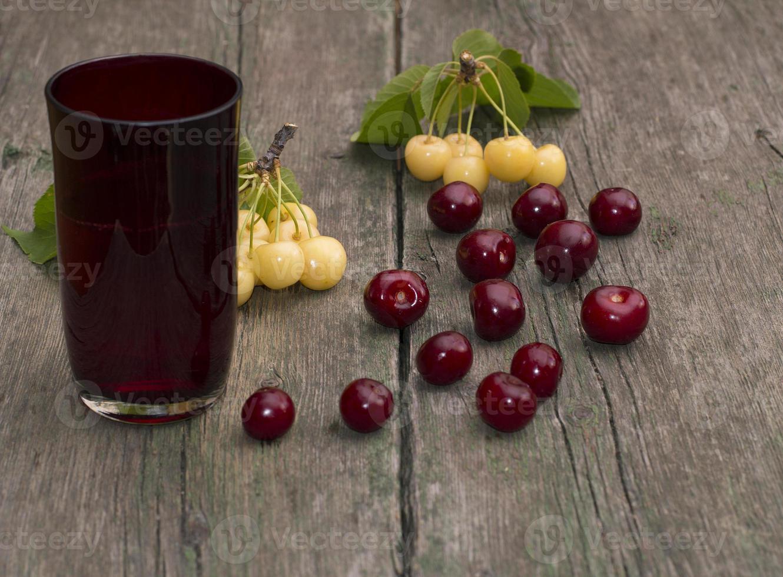 copo de suco e frutas sobre uma mesa de madeira foto