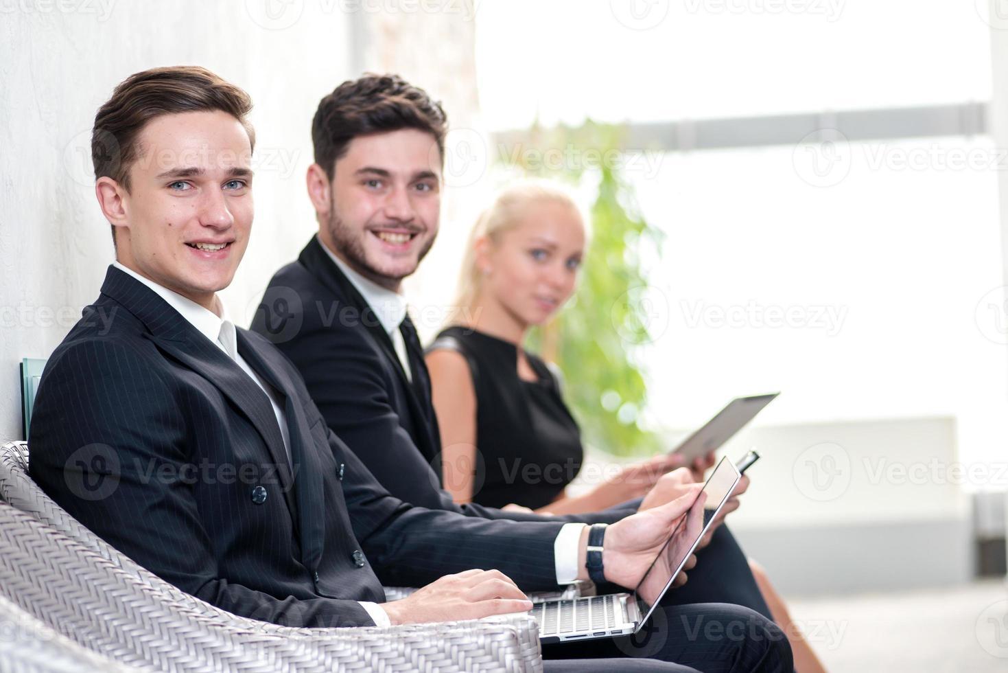 candidatos a emprego. três pessoas em trajes formais esperando no escritório foto