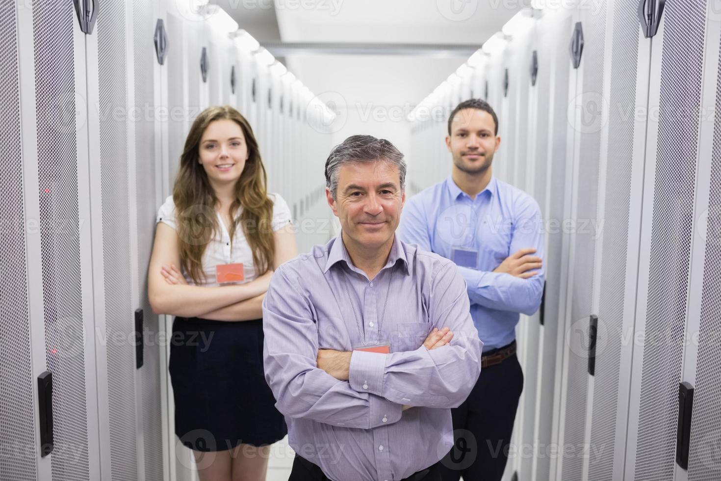 três pessoas sorridentes em pé no centro de dados foto