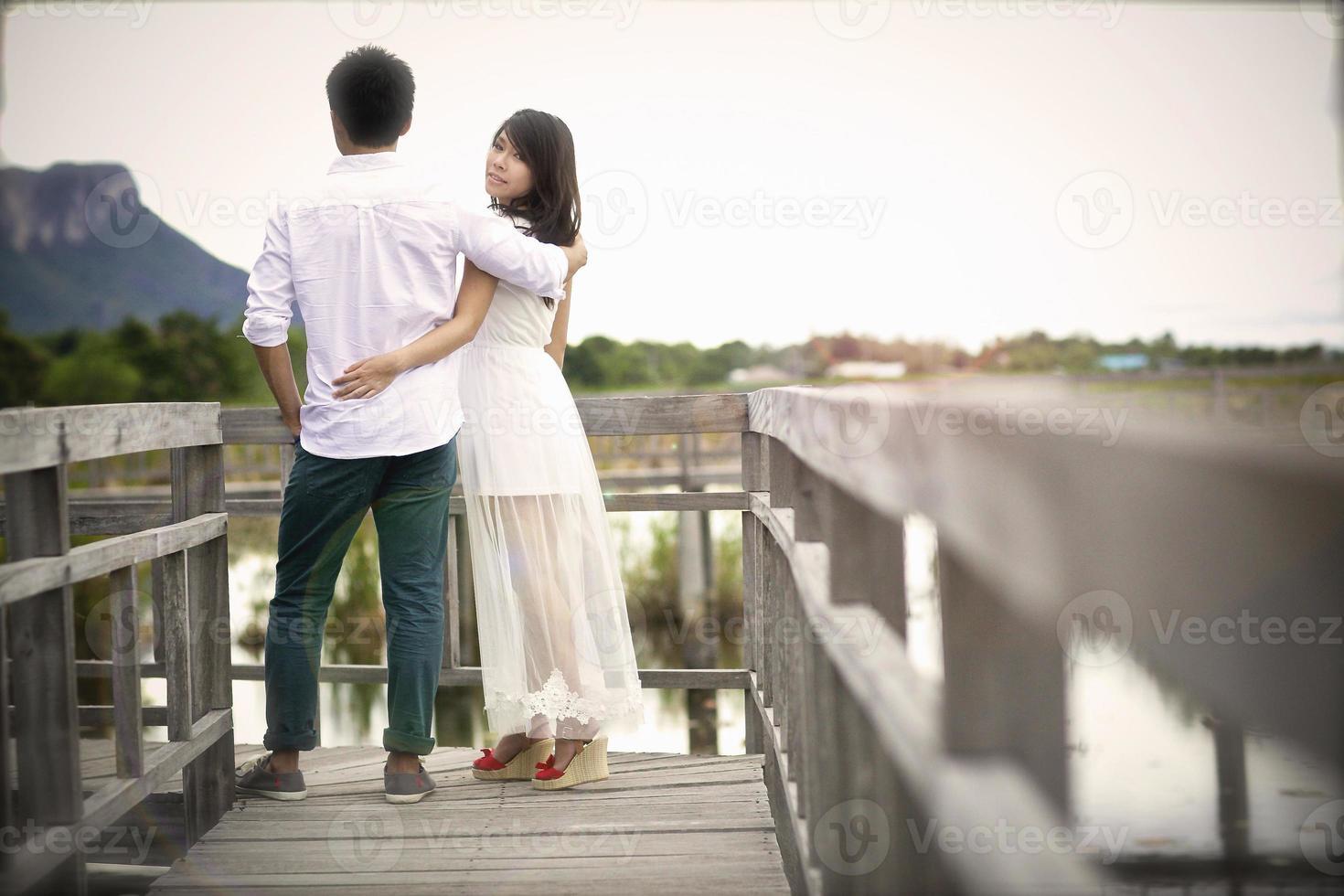 lindo casal na ponte de madeira foto