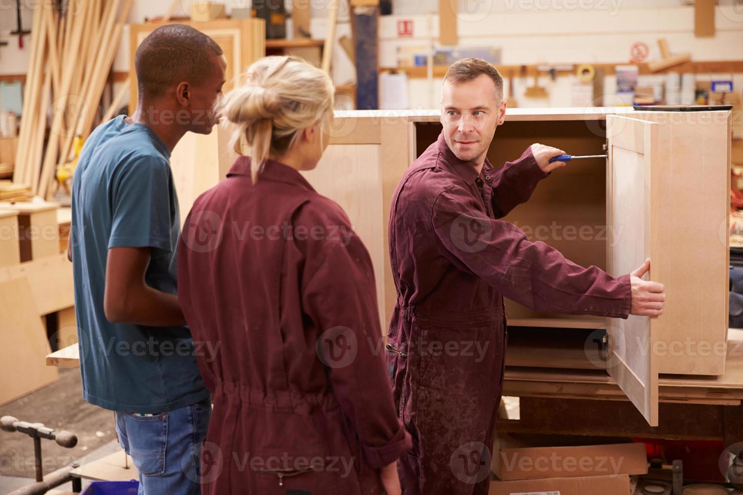 carpinteiro com aprendizes construindo móveis na oficina foto