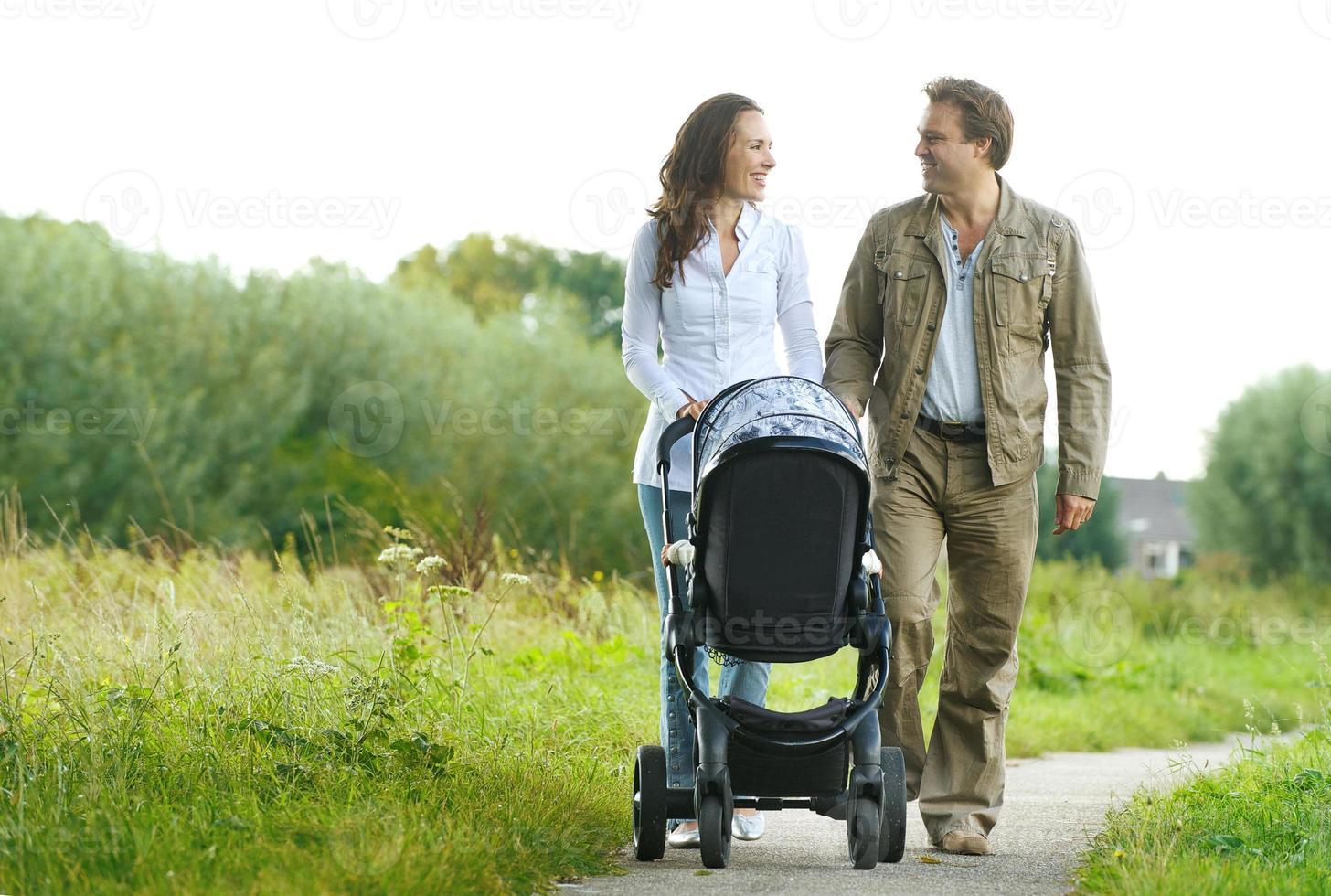 feliz homem e mulher caminhando com carrinho de bebê ao ar livre foto