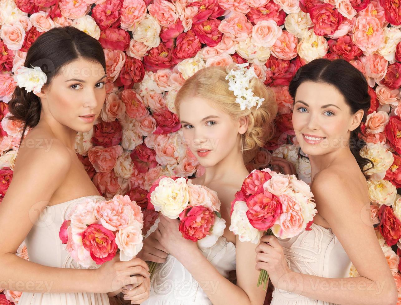 três mulheres com fundo cheio de rosas foto