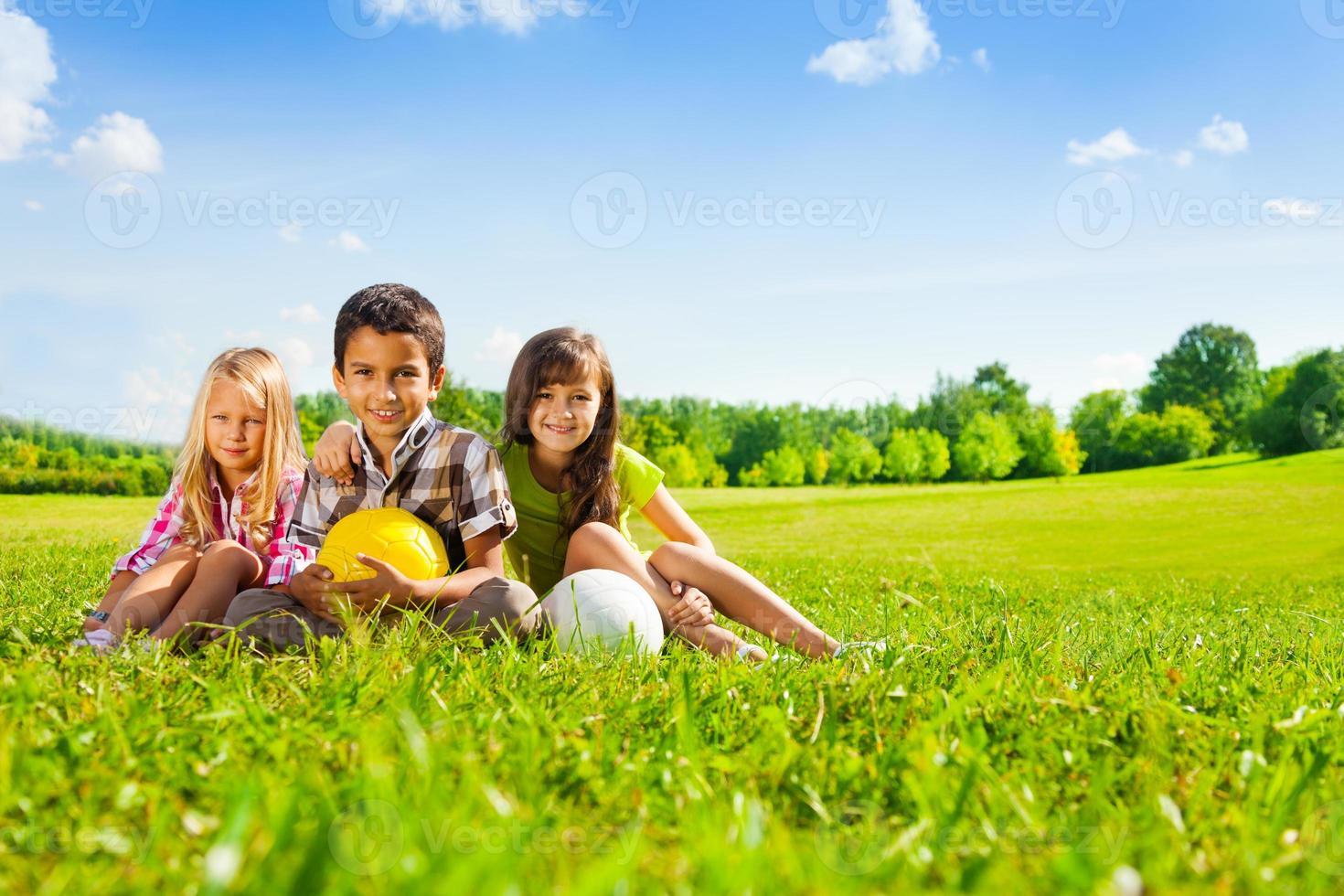 crianças sentam na grama com bolas de esporte foto