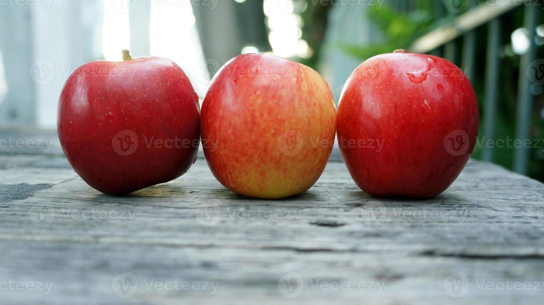 três maçãs vermelhas em cima da mesa de madeira foto