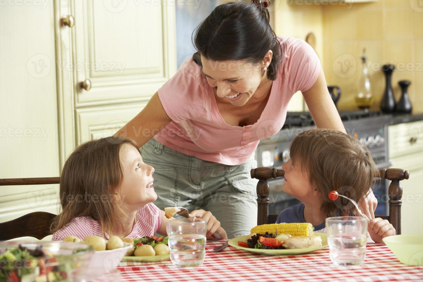 mãe servindo refeição para crianças na cozinha foto