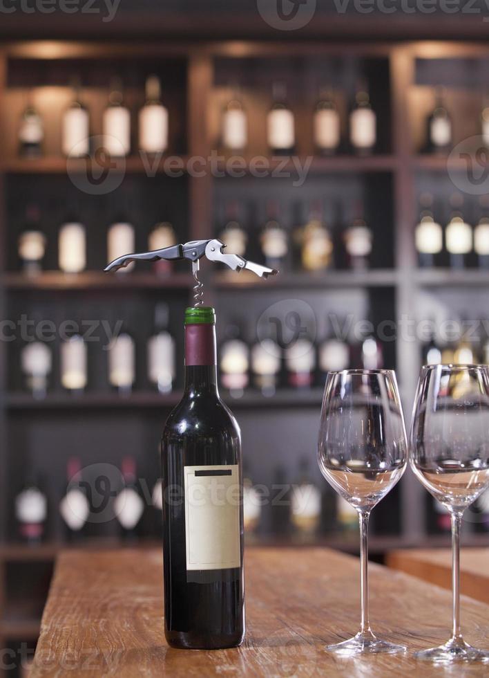 garrafa de vinho com dois copos e saca-rolhas foto