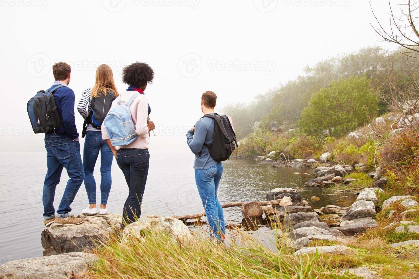 dois casais admirando a vista à beira do lago foto