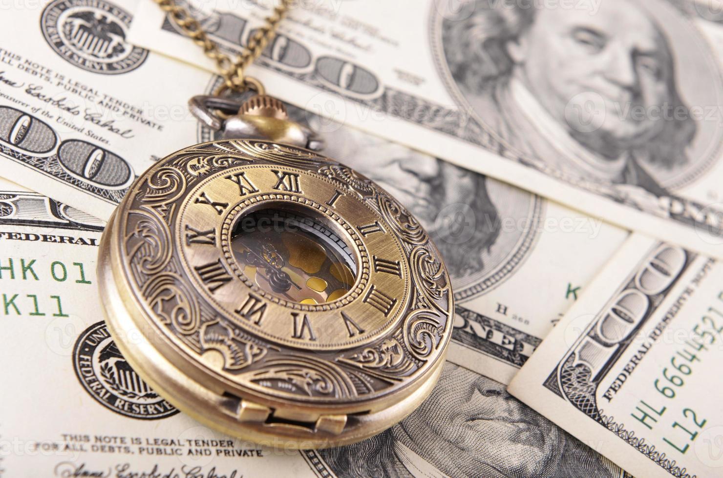 relógio de bolso na pilha de dinheiro foto