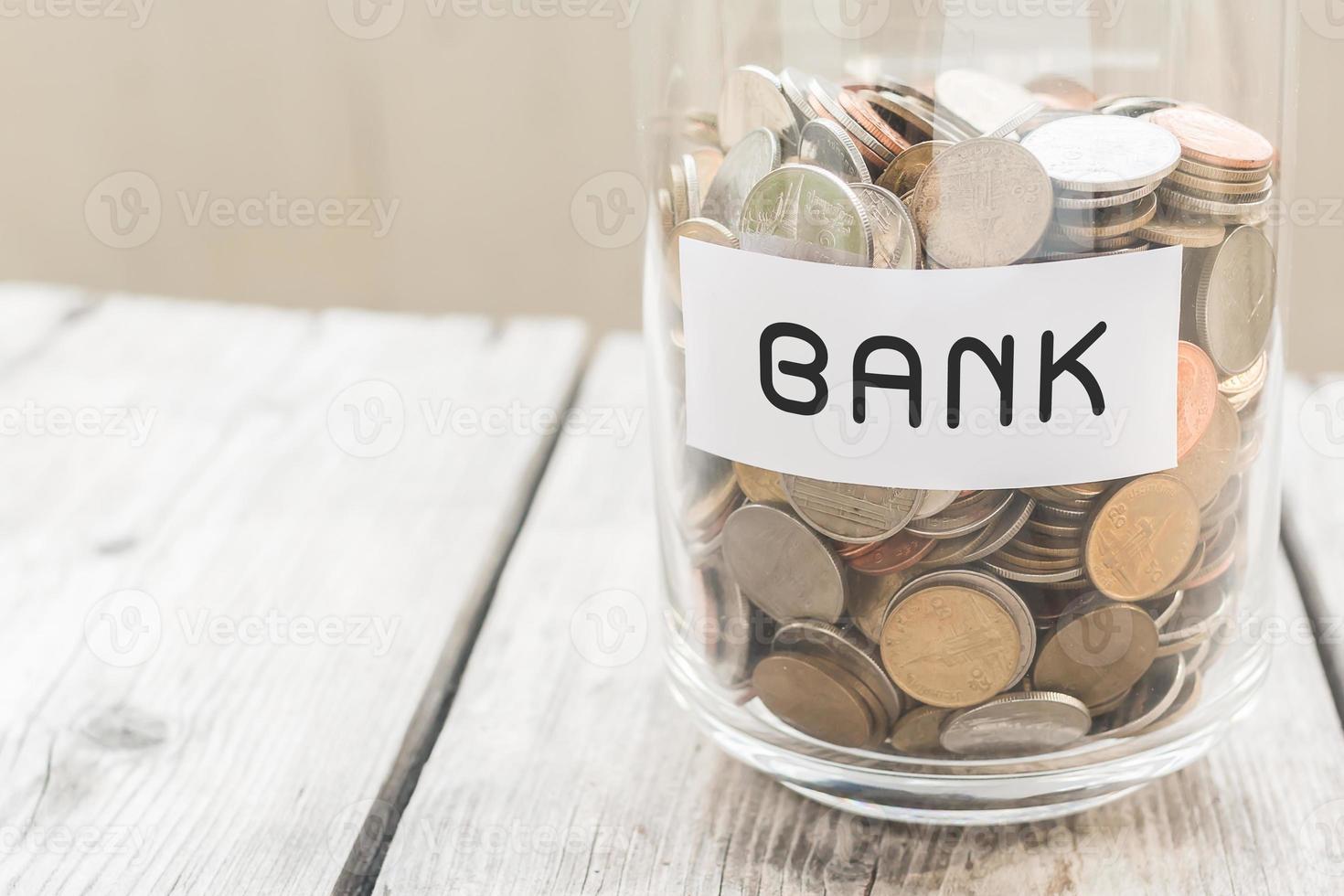 frasco de dinheiro com moedas na mesa de madeira foto