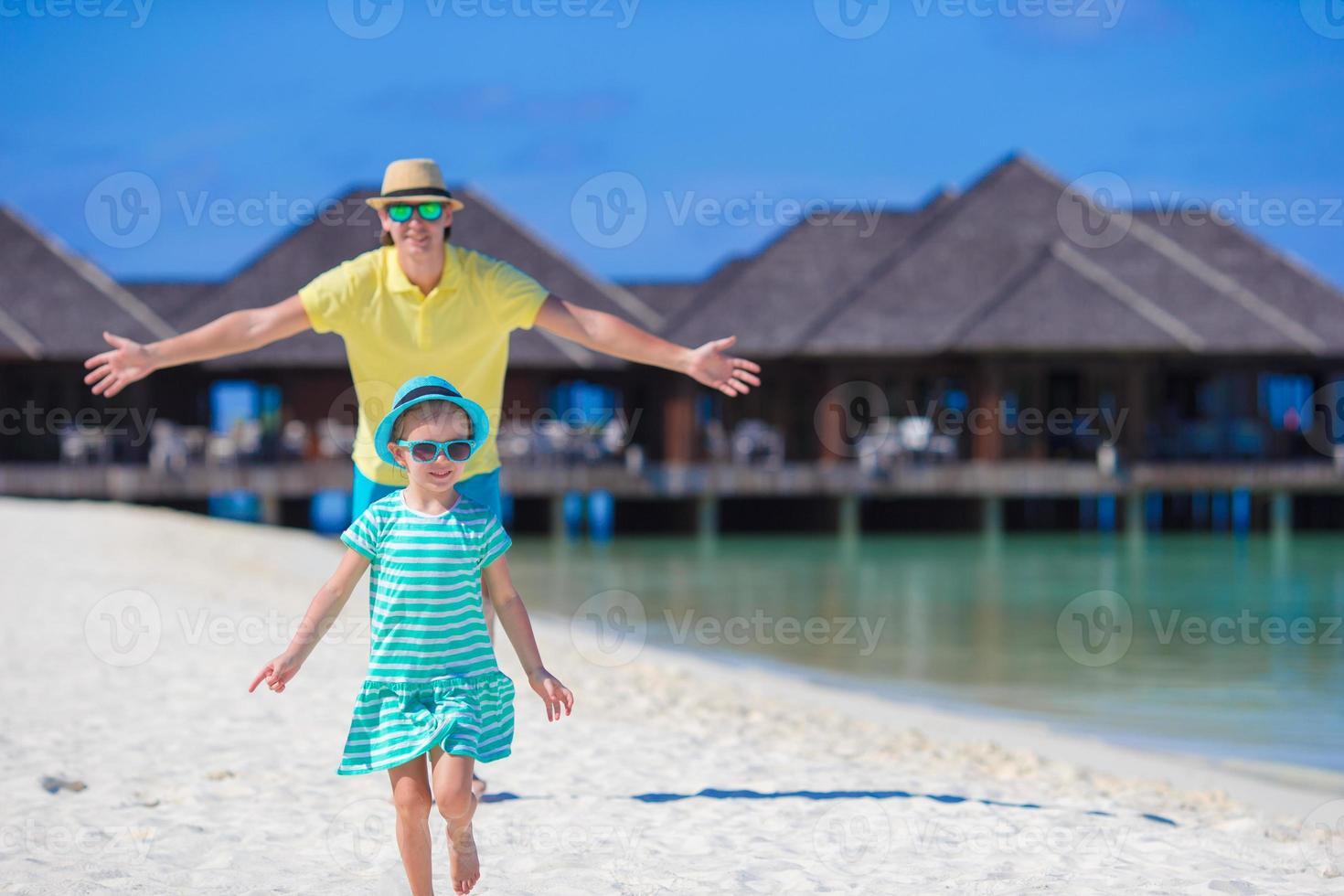 jovem pai e filha na praia tropical foto