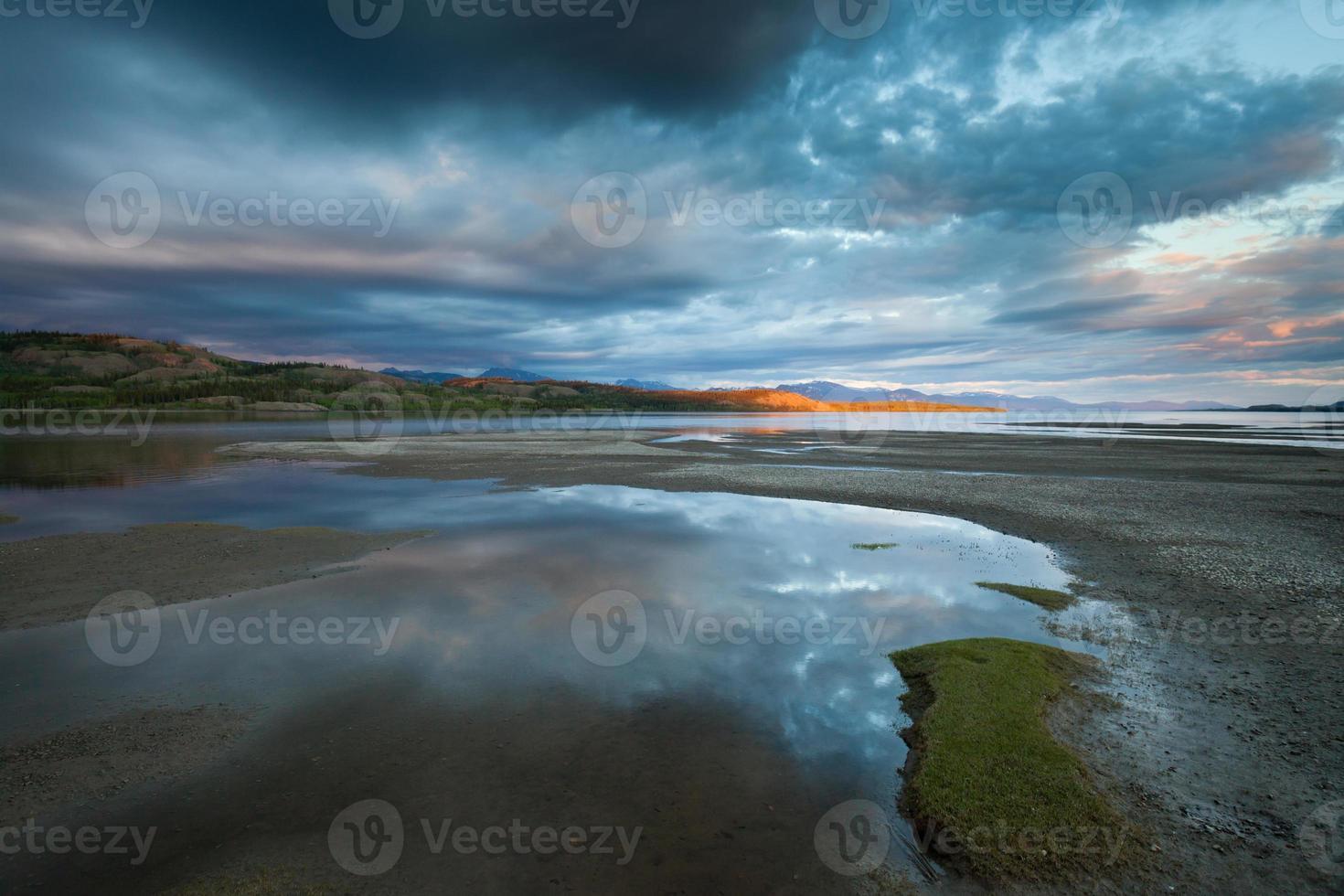 raio de sol dourado e céu dramático no lago laberge foto