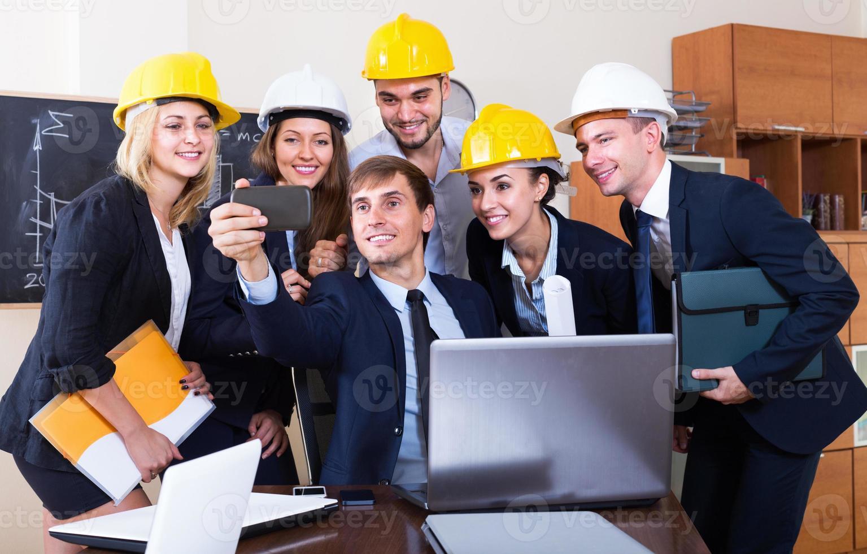 equipe de engenheiros posando e fazendo selfie foto