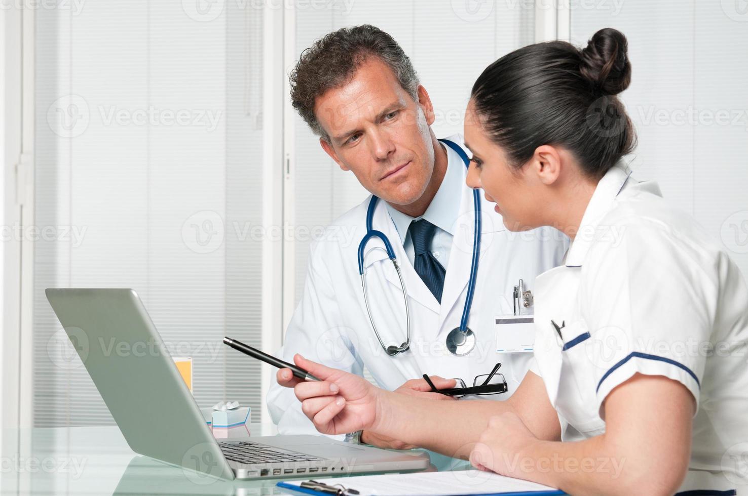 médico e enfermeira trabalhando no laptop foto