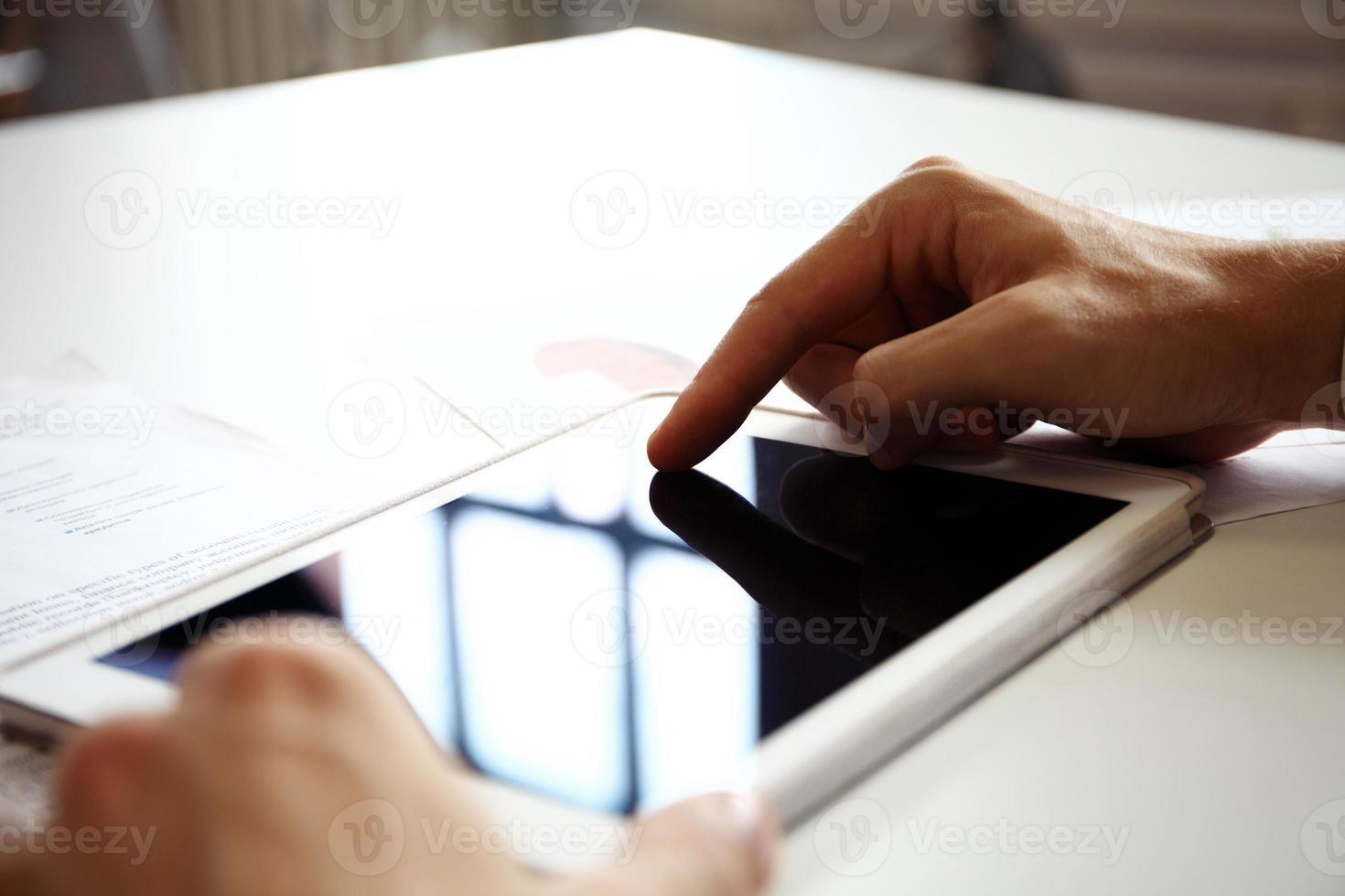dedo de empresário, apontando para a tela de um tablet pc foto