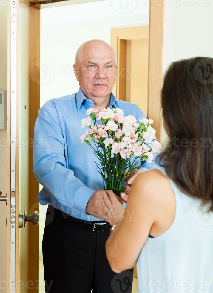 homem maduro dando ramo de flores para mulher foto