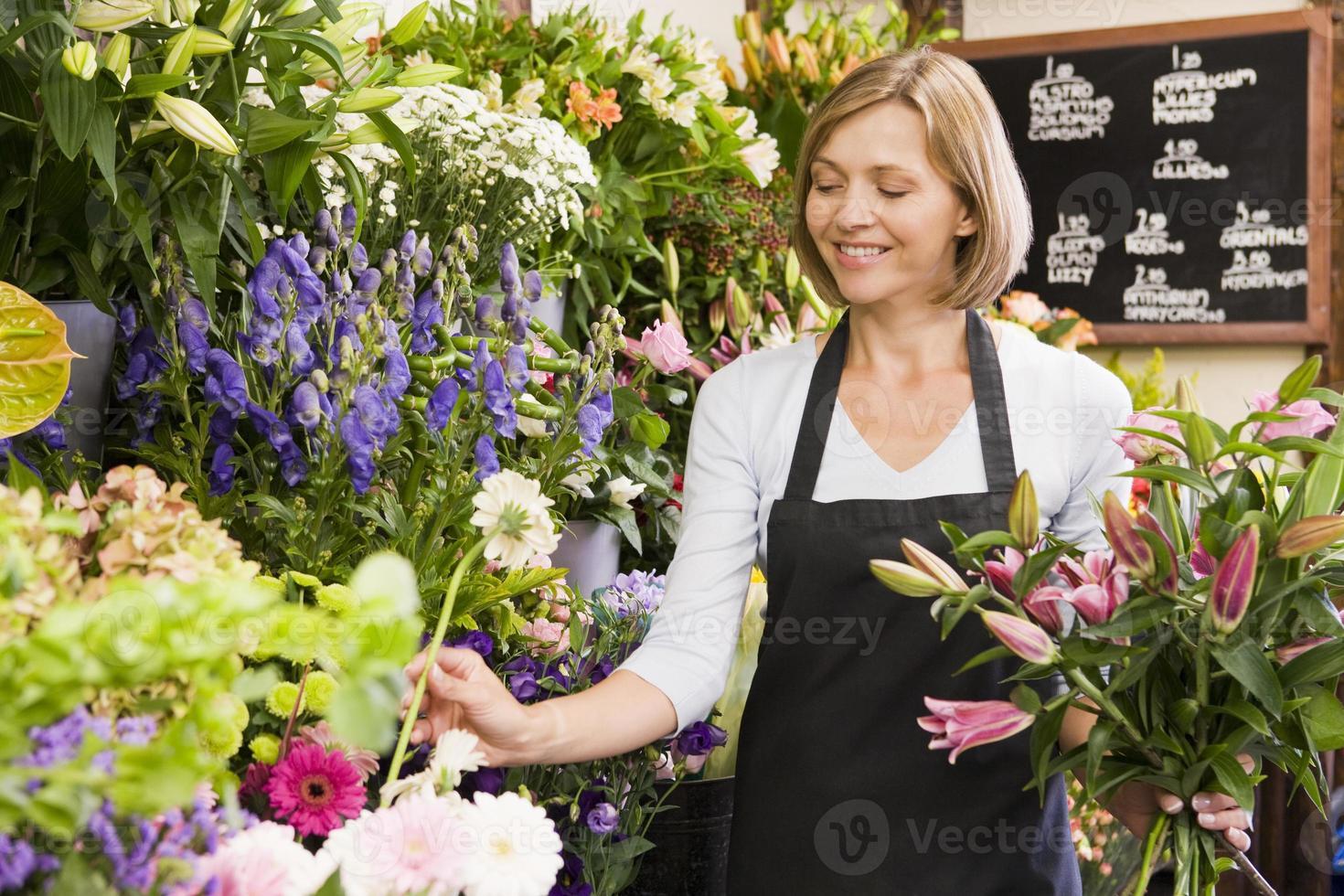 mulher que trabalha na loja de flores sorrindo foto