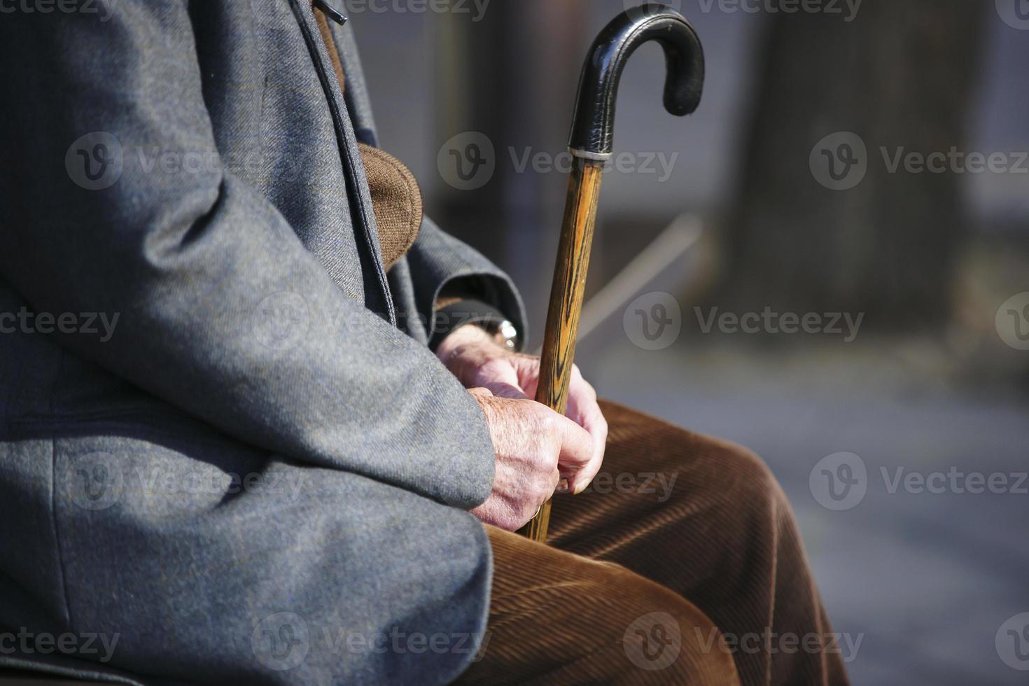 homem sênior com uma bengala, sentado no banco de madeira foto