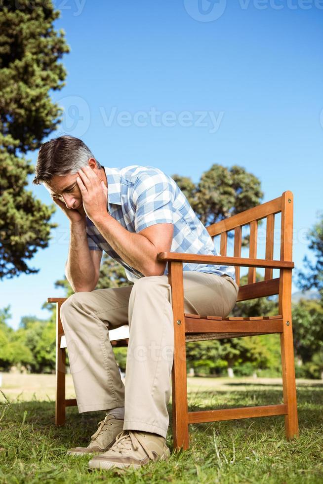 chateado homem sentado no banco do parque foto