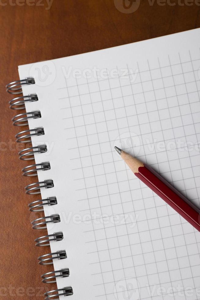 bloco de notas e lápis na mesa foto